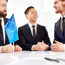 Image of European flag and business documents on workplace with three partners negotiating on background
